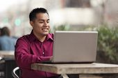 stock photo of telecommuting  - Stock photo of a happy Hispanic businessman looking down at his laptop computer while telecommuting at an internet cafe - JPG