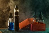 Electronic Cigarette And Bottles With Vape Liquids, Two Of Them Into Opened Gift Box, Surrounded By  poster