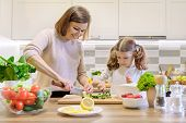Mother And Child Cooking Together At Home In Kitchen. Healthy Eating, Mother Teaches Daughter To Coo poster