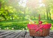 A Wooden Picnic Table With  Picnic Basket poster