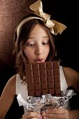 girl with the big chocolate  and with  bow on a head looking at chocolate
