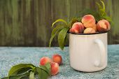 Homemade Peaches With Leaves In An Enamelled White Mug Close-up And Copy Space. Beautiful Juicy Ripe poster