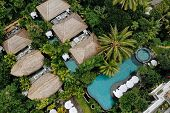 Aerial View Of Luxury Hotel With Straw Roof Villas And Pools In Tropical Jungle And Palm Trees. Luxu poster