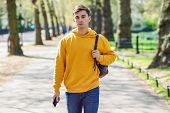 Young Urban Man Using Smartphone Walking In Street In An Urban Park In London. poster