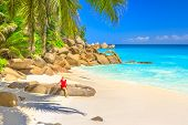 Summertime In Seychelles. Attractive Female In Red Dress Sunbathes On Boulder In Anse Georgette, A P poster