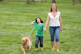foto of mother child  - Mother and Daughter Walking the Dog in the Park - JPG
