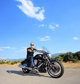 A biker riding a customized motorcycle on an open road, shot with a tilt and shift lens