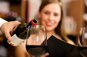 stock photo of waiter  - Waiter pouring red wine to a woman - JPG