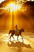 stock photo of bareback  - woman in medieval clothing backlit by sunlight on beach - JPG