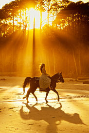 pic of bareback  - woman in medieval clothing backlit by sunlight on beach - JPG