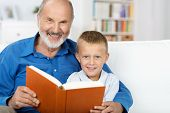 stock photo of storytime  - Elderly granfather and grandson enjoying a book together as they sit reading on a couch in the living room - JPG
