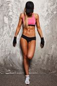 pic of stretching exercises  - Sporty woman in pink top with beautiful beautiful body against concrete wall - JPG