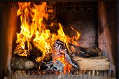 stock photo of furnace  - Fireplace or furnace invites you with its cozy blazing fire to warm up - JPG