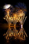 image of guy fawks  - Golden and Blue Fireworks reflected in a murky lake - JPG