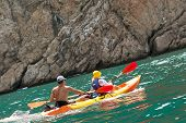 stock photo of canoe boat man  - Pair young men in a boat with a kayak paddle in hand - JPG