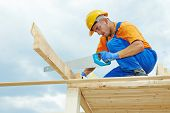 stock photo of reconstruction  - construction roofer carpenter worker sawing wood board with hand saw on roof installation work - JPG