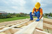 stock photo of reconstruction  - construction roofer carpenter worker hammering wood board with hammer and nail on roof installation work - JPG