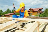 image of girder  - roofer carpenter worker nailing wood board with hammer on roof installation work - JPG