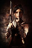 foto of gothic female  - Portrait of a beautiful steampunk woman holding a gun over grunge background - JPG