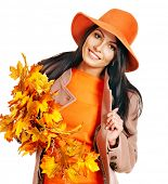 stock photo of overcoats  - Woman wearing overcoat holding  orange leaves - JPG