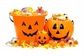 stock photo of scary face  - Group of Halloween Jack o Lantern candy holders and pile of candies - JPG
