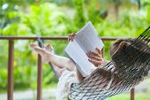 Lady reading the book in the hammock