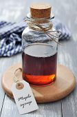 foto of maple syrup  - Maple syrup in glass bottle on a wooden background