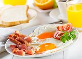 image of continental food  - Fried eggs with bacon and vegetables on a plate - JPG