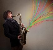 stock photo of saxophone player  - Attractive young musician playing on saxophone while colorful abstract lines exploding - JPG