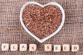 stock photo of flaxseeds  - Flax seed in cup in the shape of heart on sack cloth - JPG
