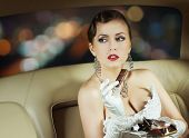 foto of superstars  - Beautiful and rich superstar girl sitting in a retro car and eating a chocolate - JPG