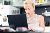 picture of independent woman  - Business woman working remotly from her dining table - JPG
