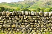 stock photo of old stone fence  - Dry stone wall with no mortar from north of England in the Lake District National Park Cumbria - JPG