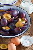 stock photo of baking soda  - Ingredients to bake a plum cake on a rustic wooden table - JPG