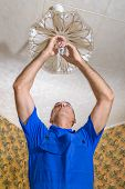 foto of electrician  - The electrician replaces a bulb in a chandelier - JPG