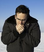 picture of frostbite  - A man outside in the winter is warming his hands by breathing on them - JPG