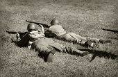 stock photo of battlefield  - Two World War 2 era soldiers on the ground shooting - JPG