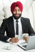 image of indian money  - Young indian businessman with money in office. ** Note: Soft Focus at 100%, best at smaller sizes - JPG