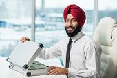 stock photo of indian money  - Young indian businessman with suitcase full of money - JPG