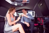 stock photo of limousine  - Happy couple drinking champagne in limousine on a night out - JPG