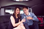 picture of limousine  - Happy friends drinking champagne in limousine on a night out - JPG