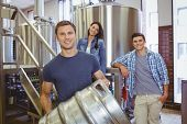 image of keg  - Young man holding keg with these colleagues behind him in the factory - JPG