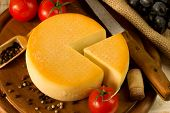 pic of meals wheels  - Cheese wheel on a wooden cutting board - JPG