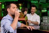 foto of bartender  - Handsome young man drinking beer while bartender tapping beer on the background - JPG