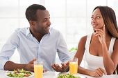 image of heterosexual couple  - Beautiful young African couple sitting together at the breakfast table and talking - JPG