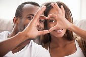 foto of heterosexual couple  - Beautiful young African couple sitting close to each other and looking through a heart shape made with their fingers - JPG