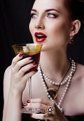 picture of ombre  - beauty stylish redhead woman with hairstyle and manicure wearing jewelry holding glass of vine - JPG