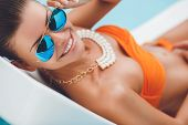 stock photo of woman bikini  - Beautiful young woman with brunette hair gathered at the nape of the neck,  blue mirror glasses, orange bikini