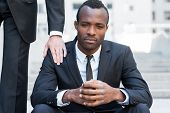 picture of frustrated  - Frustrated young African man in formalwear sitting on staircase while someone touching his shoulder with hand - JPG