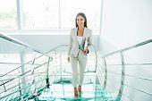 image of bannister  - Beautiful young businesswoman in formalwear moving up by staircase and smiling - JPG